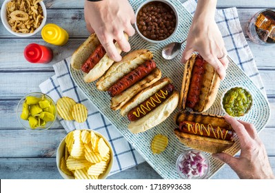 A top down view of a platter of gourmet hotdogs with hands helping themselves to a hotdog.