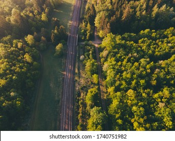 Top down view of the railway line and footpath through the forest. Aerial view of train tracks in a morning sunny forest near Munich in Bavaria, Germany. Summer Season