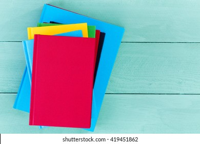 Top down view of red, yellow and blue blank hardcover books on smooth wooden table with copy space