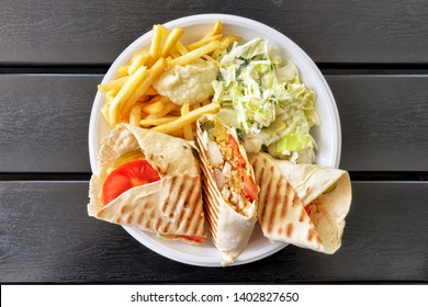 top down view of sliced chicken doner kebab sandwich on white plate in natural light on wooden table background turkish middle east arabian national food concept overview of street fast food meal