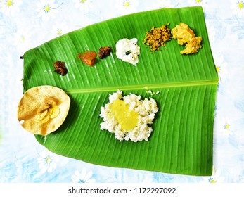 Top down view of South Indian lunch on plantain leaf. Curries are served in one half, rice in the other. Traditional Kerala sadya on fresh green plantain leaf, overhead composition.