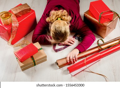 Top down view of unrecognizable woman housewife tired of wrapping Christmas presents and lying down on floor. Seasonal holidays depression concept.