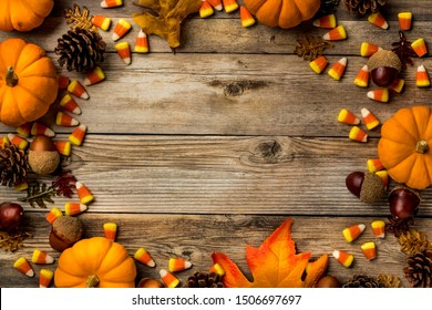 Top down view of a variety of autumn decorations forming a border against a wooden background and copy space in the middle.