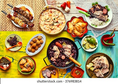 Top down view of various home made Brazilian recipes cooked and displayed on colorful textures and tablecloths
