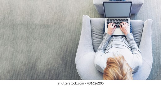Top down view of young blond person typing on laptop computer