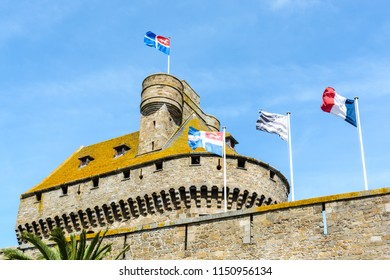 The top of the dungeon of the castle of Duchess Anne of Brittany in the old town of Saint-Malo, France, with the flag of the city blowing in the wind along with the Breton and French flags.
