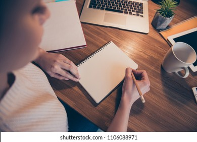 Top first person view of woman having pen in hands organizing her week writing list to do having empty page space, portrait with copyspace, sitting in workplace workstation