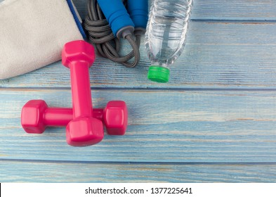 Top or flat lay view of dumbbells, towel, water and skipping rope with copy space area on blue wooden background. Healthy concept. Selective focus.