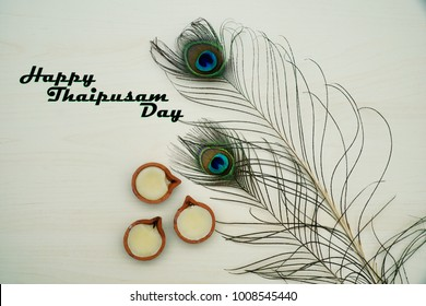 Top or flat lay view of a peacock feathers on a wooden background with a words HAPPY THAIPUSAM DAY. Celebrate by a hindu religions.  A religions conceptual.