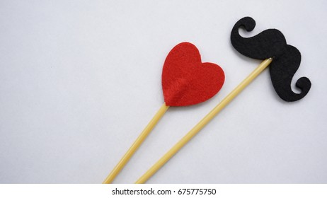 Top or flat lay view of Photo booth props black mustache and a red heart shape on a white background flat lay. Birthday parties and weddings.
