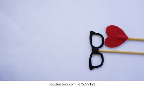 Top or flat lay view of Photo booth props red heart shape and a black spectacles on a white background flat lay. Birthday parties and weddings.