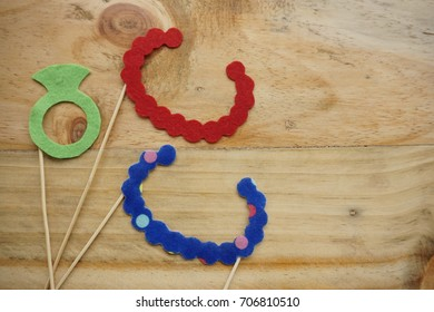 Top or flat lay view of Photo booth props a red necklace, a blue polkadot necklace and a ring on a wooden background flat lay. Birthday parties and weddings.