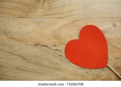 Top or flat lay view of Photo booth props a red heart shape on a wooden background flat lay. Birthday parties and weddings.