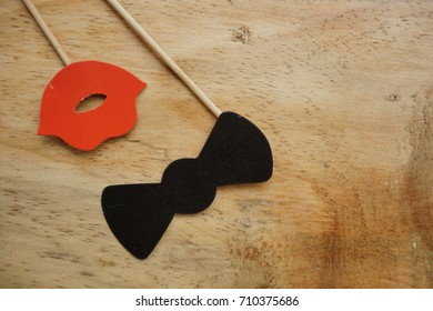 Top or flat lay view of Photo booth props a red lips and a black bow tie on a wooden background flat lay. Birthday parties and weddings.