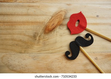 Top or flat lay view of Photo booth props a red lips and black mustache on a wooden background flat lay. Birthday parties and weddings.