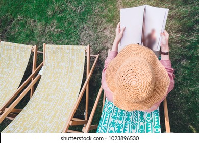 Top of girl in red shirt and wide-shoulder hat holding and reading magazine or book on chair beach at garden in relaxing time.