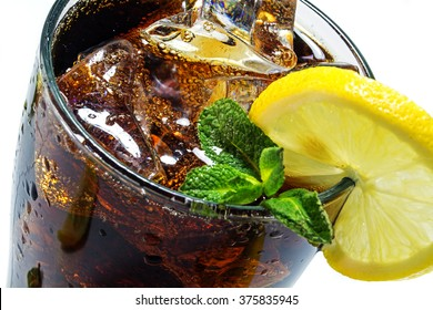top of a glass of cola or coke with ice cubes, lemon slice and peppermint garnish,  closeup with selected focus and narrow depth of field