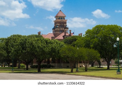 the top of the Gonzales County Texas Courthouse towering over lush green trees