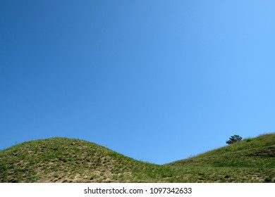 The top of a grassy double hill with blue sky in the background