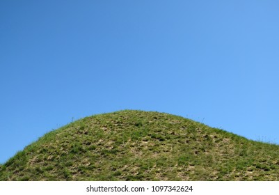 The top of a grassy hill with blue sky in the background