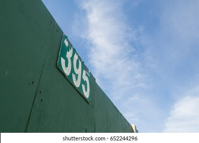 top of a green baseball field wall with a distance marker