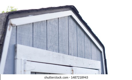 top of grey and white gambrel shed with board and batten treated siding