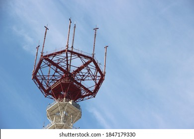 Top of high altitude Construction of TV tower painted into white and red under blue sky.