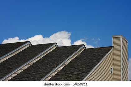 Top of house with multiple roof lines and blue sky in background