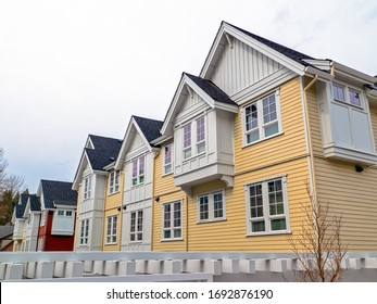 Top levels of residential townhouses on overcast sky backgfound