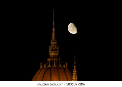 Top of the lit Hungarian Parliament building at night with half moon