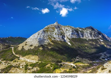 The top of the Lovcen mountain with a mobile communications tower installed, the rocky slopes are covered with green grass and trees and the road around. Vidikovac, Lovcen National Park, Montenegro.