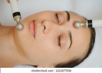 Top macro close up view of women facial massage spa procedure. Electric stimulation facial skin care. Microcurrent lift face. Beauty spa procedure. Anti aging rejuvenation non surgical treatment