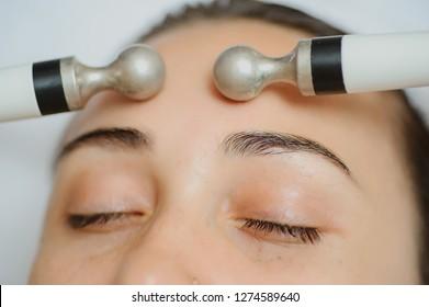 Top macro close up view of women facial massage spa procedure. Electric stimulation facial skin care. Microcurrent lift face. Beauty spa procedure. Anti a rejuvenation non surgical treatment