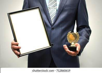 Top manager award mockup. Best office employee award. Business man holding empty blank photo frame (gratitude letter) in one hand and gold medal in another one. Gratitude concept. Grateful letter.