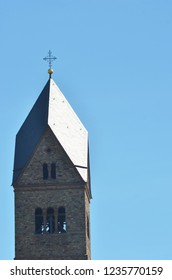 A top of a medieval church tower, complete with a cross, is seen against a clear blue sky. Sunshine is reflected off the roof. Bells can be seen through the window.