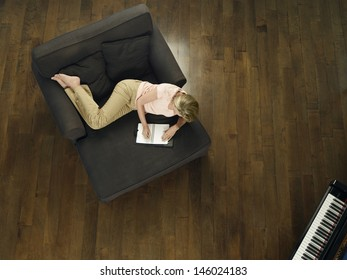 Top of a middle aged woman writing in notebook on sofa at home