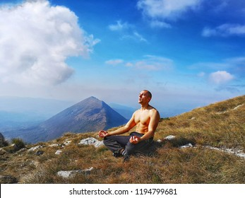 Top Naked Man, Meditating On The Top Of The Mountain. White Clouds, Blue Sky And Huge Mountain In Background.