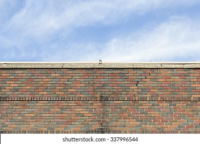 Top of an Old Brick Building against a Cloudy Blue Sky