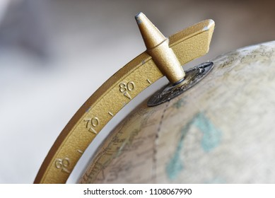 Top of old globe, with golden colored latitude measurement device attached.