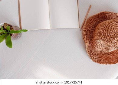 Top of open blank book or notebook with wooden pencil and wide-shoulder hat on white table in flat lay concept.