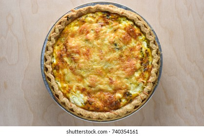 Top or overhead view of an isolated healthy vegetarian spinach quiche fresh from the oven with wooden background.  Ingredients red pepper, spinach, feta parmesan cheese, and pie crust.