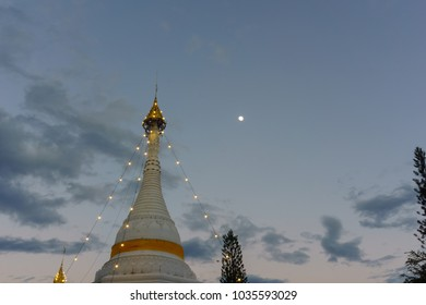 top of pagoda in temple decorated with light at night when full moon.Mae Hong Son,Thailand.
