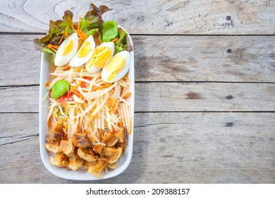 Top of papaya salad with egg and fried meat thai food style on wood background
