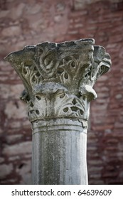 The top part of an ancient column against an old wall near the Cathedral of Sacred Sofia, Istanbul, Turkey