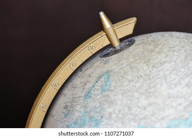 Top part of old globe, with focus on golden latitude measurement tool.