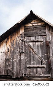 Top part old rustic wooden house - an attic with small door. View from outside.