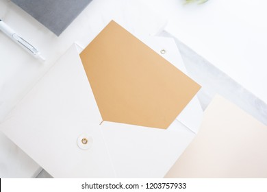 top perspective view of blank golden card in white envelop on two layer step of marble table top.Mock up template for display of design,modern business items