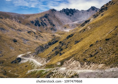 The top portion of the road from Queenstown to The Remarkable Ski Area is winding through rough mountain range terrain with majestic mountain peaks in the distance.