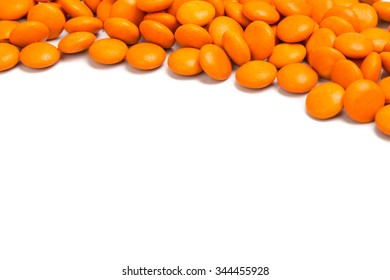 Top right frame of orange color chocolate coated candy on white background with space for text