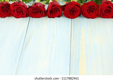 Top of a row of red roses on light blue wooden table.